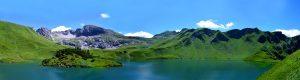 negeri 1000 pulau, gunung di pinggir laut dan di atasnya awan biru cerahnya, pulau luas dengan pemandangan yang memukau, hutan yang lebat penuh dengan pohon.
